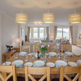 Esempio di una sala da pranzo costiera con pareti bianche, parquet chiaro e pavimento blu