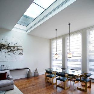 Aménagement d'une grande salle à manger ouverte sur le salon contemporaine avec un mur blanc, un sol en bois brun et un sol orange.