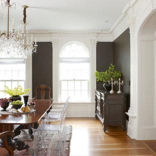 Huge elegant medium tone wood floor and brown floor enclosed dining room photo in Boston with black walls