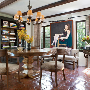 Example of a tuscan terra-cotta floor dining room design in Los Angeles with white walls