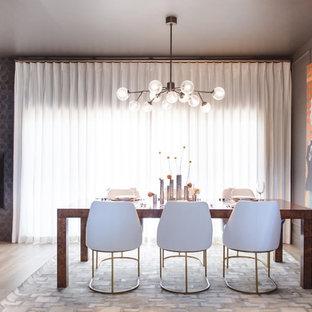 Immagine di una sala da pranzo aperta verso il soggiorno chic di medie dimensioni con pareti grigie, pavimento in gres porcellanato, camino classico, cornice del camino piastrellata e pavimento beige