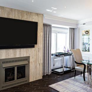 Immagine di una sala da pranzo aperta verso il soggiorno classica con pareti viola, pavimento con piastrelle in ceramica, camino classico, cornice del camino piastrellata e pavimento nero