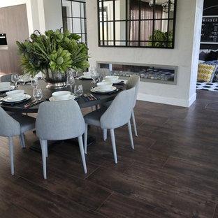 Diseño de comedor actual, de tamaño medio, abierto, con paredes blancas, suelo de baldosas de porcelana, chimenea lineal, suelo marrón y marco de chimenea de hormigón
