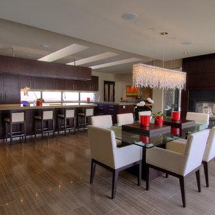 Immagine di una grande sala da pranzo aperta verso la cucina minimal con pareti beige, pavimento in gres porcellanato, camino bifacciale, cornice del camino in pietra e pavimento marrone
