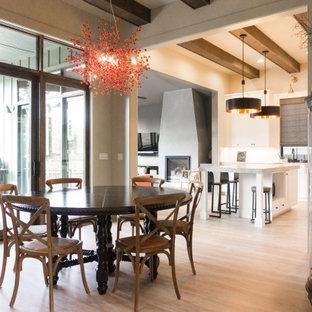 Foto di una sala da pranzo aperta verso la cucina eclettica di medie dimensioni con pareti gialle, pavimento in vinile, camino classico, cornice del camino in intonaco e pavimento beige