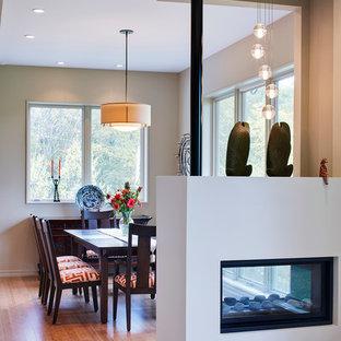 Modern inredning av en mellanstor matplats med öppen planlösning, med beige väggar, en dubbelsidig öppen spis, mörkt trägolv, en spiselkrans i gips och beiget golv