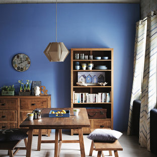 Photo of a scandinavian dining room in London with blue walls and white floors.