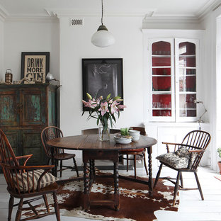 This is an example of a traditional dining room in London with white walls, painted wood flooring and a standard fireplace.