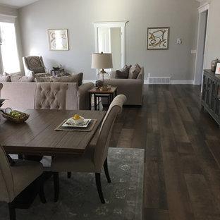 Immagine di una grande sala da pranzo moderna con pareti grigie, pavimento in laminato, pavimento beige, camino classico e cornice del camino piastrellata