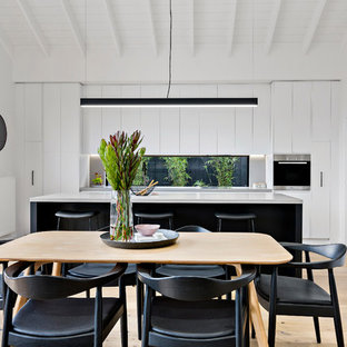 Design ideas for a contemporary open plan dining in Melbourne with white walls, light hardwood floors and beige floor.