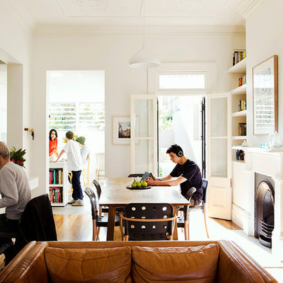 Example of a trendy medium tone wood floor great room design in Sydney with white walls and a standard fireplace