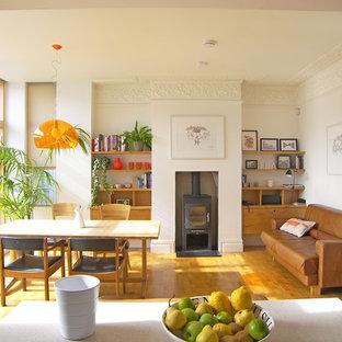 Новый формат декора квартиры: гостиная-столовая в современном стиле с паркетным полом среднего тона, печью-буржуйкой и белыми стенами