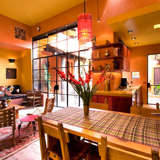 Aménagement d'une salle à manger ouverte sur le salon éclectique de taille moyenne avec un mur orange et un sol en brique.