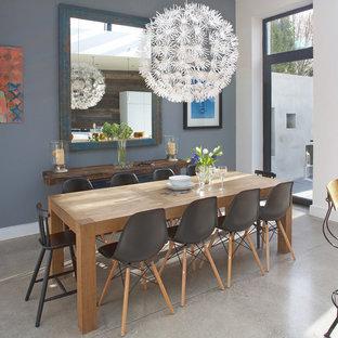 Immagine di una sala da pranzo aperta verso la cucina contemporanea di medie dimensioni con pareti grigie, pavimento in cemento e nessun camino
