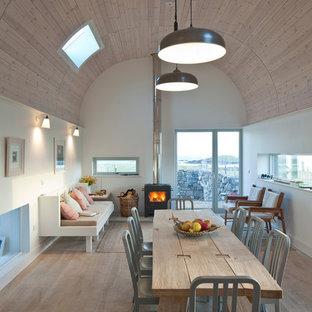 Ejemplo de comedor contemporáneo, de tamaño medio, abierto, con paredes blancas, suelo de madera clara y estufa de leña