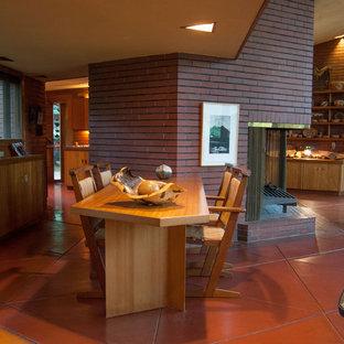 Modernes Esszimmer mit Kaminumrandung aus Backstein und rotem Boden in Cleveland