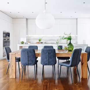 This is an example of a contemporary kitchen/dining combo in Melbourne with white walls, dark hardwood floors and brown floor.