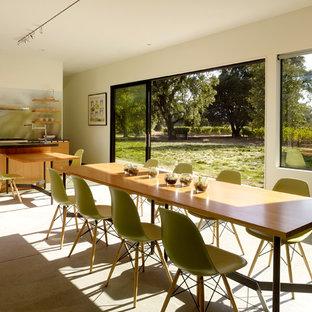 Immagine di una sala da pranzo aperta verso la cucina minimalista di medie dimensioni con pavimento in cemento, pareti beige, nessun camino e pavimento grigio