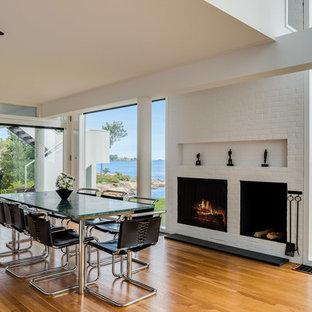 Idée de décoration pour une salle à manger ouverte sur le salon minimaliste avec un mur blanc, un sol en bois brun, une cheminée standard et un manteau de cheminée en brique.