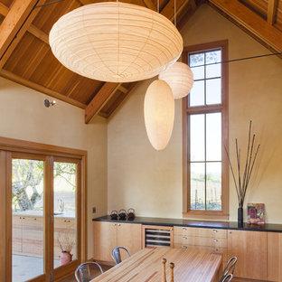 Cette image montre une salle à manger ouverte sur la cuisine rustique de taille moyenne avec un mur beige.