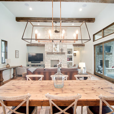 Mid-sized country light wood floor and brown floor great room photo in Austin with white walls and no fireplace