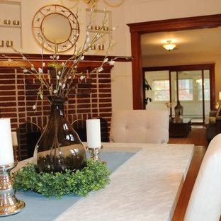 Modelo de comedor bohemio, de tamaño medio, cerrado, con paredes blancas, suelo de madera en tonos medios, chimenea de esquina y marco de chimenea de ladrillo