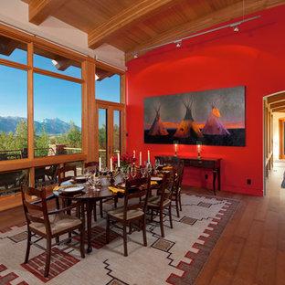 Foto di una sala da pranzo aperta verso il soggiorno rustica con pareti rosse e pavimento in legno massello medio