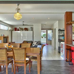 Immagine di una sala da pranzo aperta verso la cucina tropicale di medie dimensioni con pareti bianche e pavimento in vinile