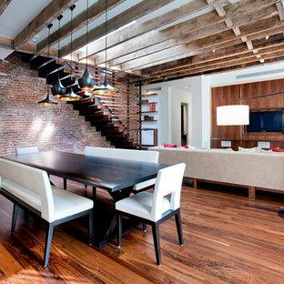 Immagine di una sala da pranzo aperta verso il soggiorno industriale con parquet scuro, pareti bianche e nessun camino