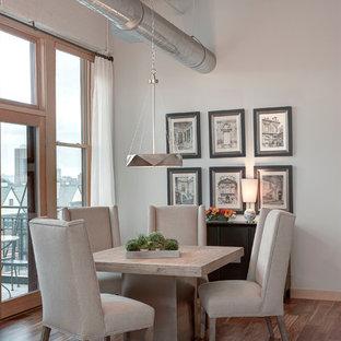 Modelo de comedor urbano, pequeño, sin chimenea, con paredes grises, suelo de madera en tonos medios y suelo marrón