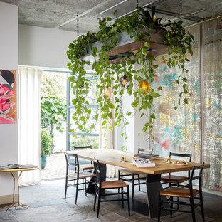 Immagine di una sala da pranzo eclettica con pareti bianche e pavimento grigio