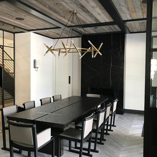 Foto de comedor industrial, cerrado, con paredes blancas, chimenea tradicional, marco de chimenea de piedra y suelo gris