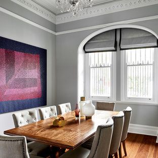 Inspiration for a large transitional dining room in Sydney with grey walls, medium hardwood floors and brown floor.