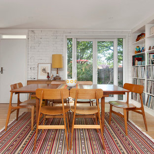 This is an example of a scandinavian dining room in Canberra - Queanbeyan with white walls and light hardwood floors.