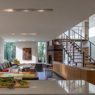 Ispirazione per una sala da pranzo aperta verso il soggiorno minimalista con pareti bianche, pavimento in cemento, camino ad angolo, cornice del camino in legno e pavimento grigio