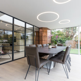 Large contemporary enclosed dining room in London with white walls, light hardwood flooring, no fireplace and beige floors.