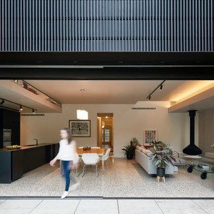 Idee per una grande sala da pranzo aperta verso il soggiorno design con pareti bianche, pavimento in cemento, camino sospeso e pavimento grigio