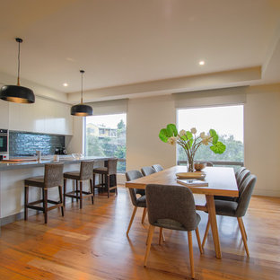 Photo of a transitional dining room in Melbourne with white walls, medium hardwood floors and no fireplace.