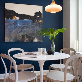 Immagine di una sala da pranzo minimal con pareti blu e pavimento in legno massello medio