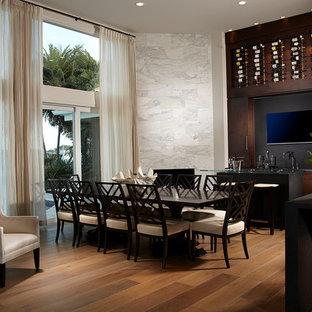 Foto di una grande sala da pranzo aperta verso il soggiorno tropicale con pareti bianche, parquet chiaro, camino ad angolo e cornice del camino in pietra