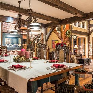 Modelo de comedor bohemio, de tamaño medio, abierto, con paredes beige, suelo de madera en tonos medios, chimenea de esquina y marco de chimenea de baldosas y/o azulejos