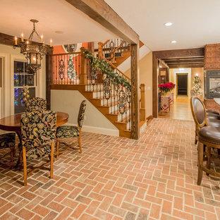 Immagine di una sala da pranzo aperta verso la cucina eclettica di medie dimensioni con pareti beige, pavimento in mattoni, camino bifacciale e cornice del camino piastrellata
