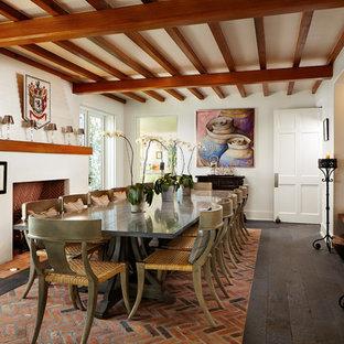 Geschlossenes, Großes Tropenstil Esszimmer mit weißer Wandfarbe, dunklem Holzboden, Kamin und Kaminsims aus Backstein in Miami