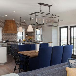 Foto di una sala da pranzo aperta verso il soggiorno stile marinaro di medie dimensioni con pareti grigie, parquet chiaro, camino classico e cornice del camino in pietra