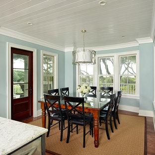 Cette image montre une salle à manger ouverte sur la cuisine ethnique avec un mur bleu et un sol en bois foncé.