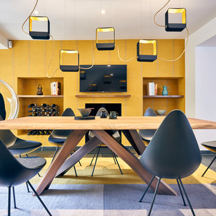 Contemporary open plan dining room in London with yellow walls, a standard fireplace and grey floors.