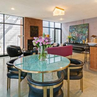 ミネアポリスの中サイズのモダンスタイルのおしゃれなダイニングキッチン (紫の壁、コンクリートの床、標準型暖炉、レンガの暖炉まわり、グレーの床) の写真