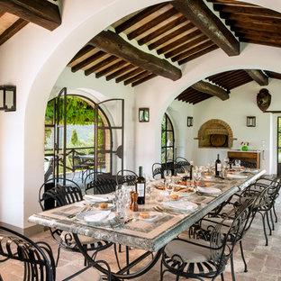Foto di una sala da pranzo mediterranea con pareti bianche e pavimento in mattoni