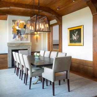 Foto på en rustik separat matplats, med vita väggar, mellanmörkt trägolv, en standard öppen spis, en spiselkrans i sten och orange golv