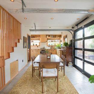 Ispirazione per una sala da pranzo aperta verso la cucina etnica con pareti bianche, pavimento in cemento e pavimento grigio